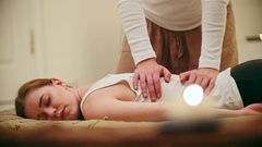 Male masseur holds the thai massage session - flexing the ribs and spine, slider Stock Footage