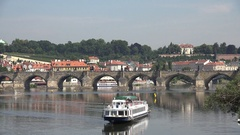 4K Touristic ferry cruise sail on Vltava river near Charles Bridge Prague emblem Stock Footage