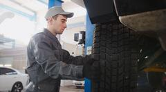 Garage automobile service - a mechanic working the wheel, close up Stock Photos