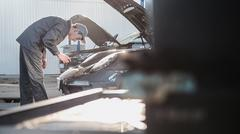 Mechanic in automobile garage checking hood for the luxury sport car Stock Photos