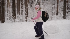 Side view of active woman doing nordic walking with ski poles in winter nature Stock Footage