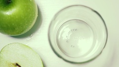 Apples green top view slow motion poured juice Stock Footage