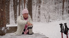 The pensioner in the winter wood. The elderly woman sits on a bench has rest and Stock Footage
