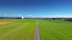 Green grass road aerial wide view horizon parabolic satellite station antenna Stock Footage