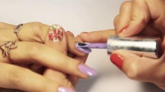 Manicurist hand paints lilac finger nail polish on white desk in cosmetic salon Stock Footage