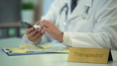Therapeutist using smartphone at work, contacting patient to inform diagnosis Stock Footage