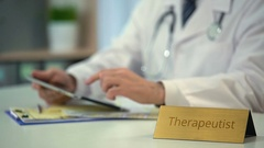 Therapeutist consulting patients online, scrolling medical news on tablet PC Stock Footage