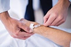 Doctor attaching iv drip on patients hand Stock Photos