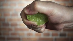 Chef's hand squeezes of green lime, close-up slow motion hd video Stock Footage