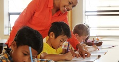 Teacher assisting school kids with their classwork in classroom Stock Footage