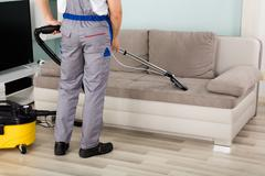 Male Worker Cleaning Sofa With Vacuum Cleaner Stock Photos