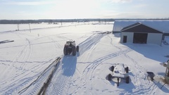 Aerial tractor with chained tree dragging in snow 4k Stock Footage