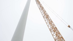 Wind Turbine Tower and a Crane. Camera Moving Down Stock Footage