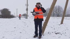 Electrician with laptop talking on smart phone under high-voltage line in winter Stock Footage