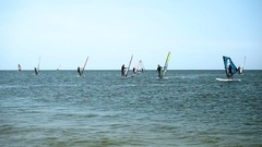 Wind-surfing. Dark silhouettes of surfers riding on sailboards on sea waves. HD Stock Footage