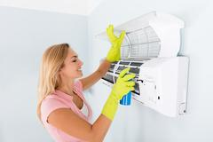 Happy Woman Cleaning The Air Conditioner Stock Photos