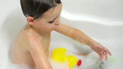 Boy playing with plastic toys in the bathtub while bathing Stock Footage