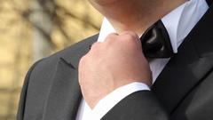 Bridegroom who arranges bow tie at the neck before going to church Stock Footage