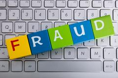 Fraud Word On Cubes Over Laptop Stock Photos