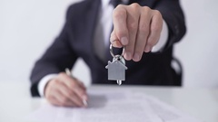 Man holding out key from house or apartment to buyer, signing mortgage agreement Stock Footage