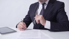 Real estate agent holding out house keys to client and signing mortgage papers Stock Footage