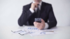Serious stock market expert checking news on smartphone, analyzing information Stock Footage