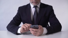 Businessman analyzing growth of production costs at enterprise, using smartphone Stock Footage