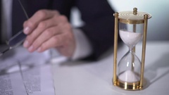 Politician reading and signing important reform document, sand flowing in clock Stock Footage