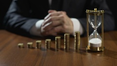Tycoon earning money on lucrative investment project, sandglass measuring time Stock Footage