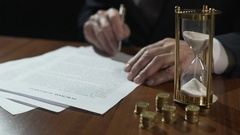 Serious businessman signing purchase agreement as time flows with sand in clock Stock Footage
