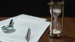 Close-up of document and hourglass on table, contract validity period expiring Stock Footage