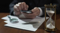 Company director viewing electronic files on gadget, sandglass measuring time Stock Footage