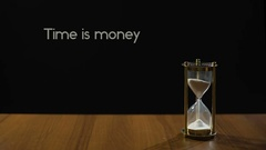 Time is money, wise phrase against black background, sand flowing in hourglass Stock Footage