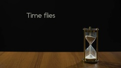 Time flies, phrase about transience of life, sand flowing in hourglass on table Stock Footage