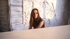 Dolly shot of beautiful girl sitting at the piano illuminated by sunlight from Stock Footage