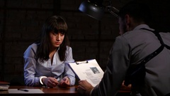 Detective man forces the girl a felon to write confession Stock Footage