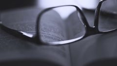 Glasses on old book - film style Stock Footage