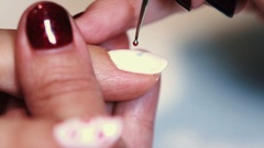 Manicure procedure female hand drawing red lips on white finger nail varnish Stock Footage