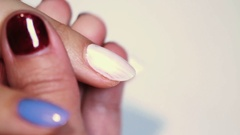 Manicure session female painting blue polish on finger nail over plain table Stock Footage