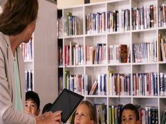 Teacher teaching school kids on digital tablet in library Stock Footage