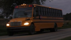 School bus driving down rural road, early morning, Indiana USA Stock Footage