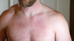 Man flexes his pectoral muscles in mirror Stock Footage