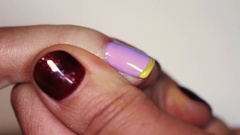 Manicure procedure woman hand drawing yellow stripe on purple finger nail polish Stock Footage