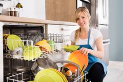 Woman Arranging Plates In Dishwasher Stock Photos