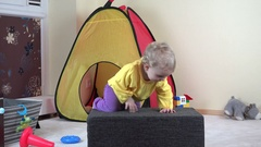 Cute toddler girl play with toy cat and climb on soft pouffe at home Stock Footage