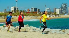 People running next to the navy blue sea, steadycam shot, slow motion shot  Stock Footage