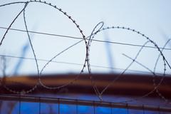 Fence with barbed wire. focus with shallow depth of field. Stock Photos