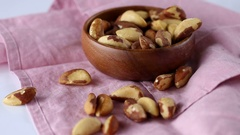 Brazil nuts falls in a wooden bowl Stock Footage