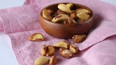 Brazil nuts in a  bowl on a pink linen napkin Stock Footage