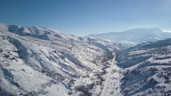 Aerial descending mountain valley road winter snow 4K Stock Footage